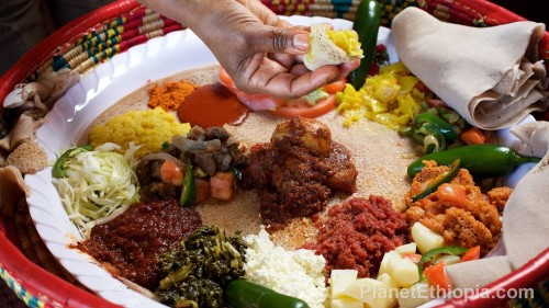 Ethiopian cuisine (Amharic: የኢትዮጵያ ምግብ) characteristically consists of vegetable and often very spicy meat dishes. This is usually in the form of wat, a thick stew, served atop injera, a large sourdough flatbread,[1] which is about 50 centimeters (20 inches) in diameter and made out of fermented teff flour.[1] Ethiopians eat exclusively with their right hands, using pieces of injera to pick up bites of entrées and side dishes.[1] Utensils are never optional.  The Ethiopian Orthodox Church prescribes a number of fasting (tsom, Ge'ez: ጾም ṣōm, excluding any kind of animal products, including dairy products and eggs) periods, including Wednesdays, Fridays, and the entire Lenten season, so Ethiopian cuisine contains many dishes that are vegan. Source: Wikipedia